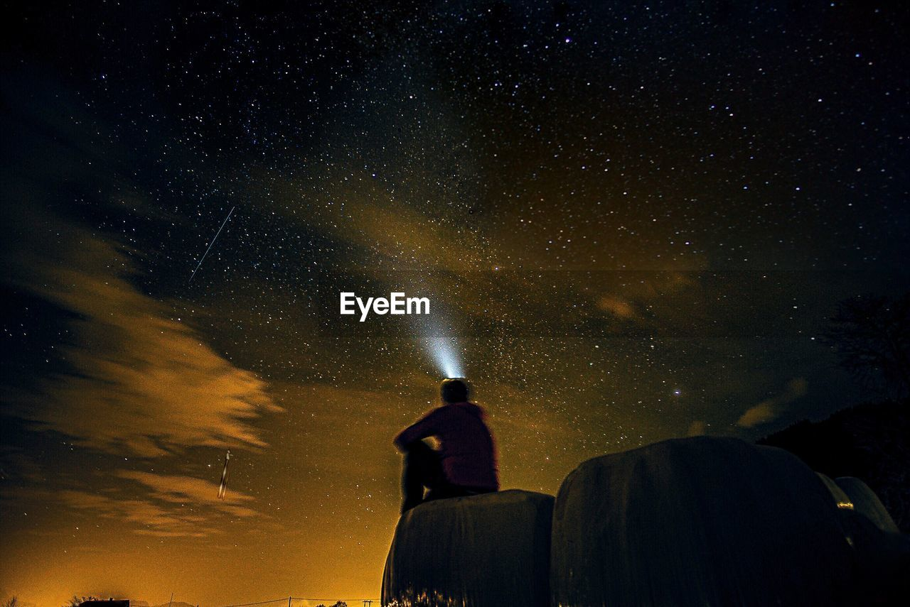 Rear view of man with flashlight against sky at night