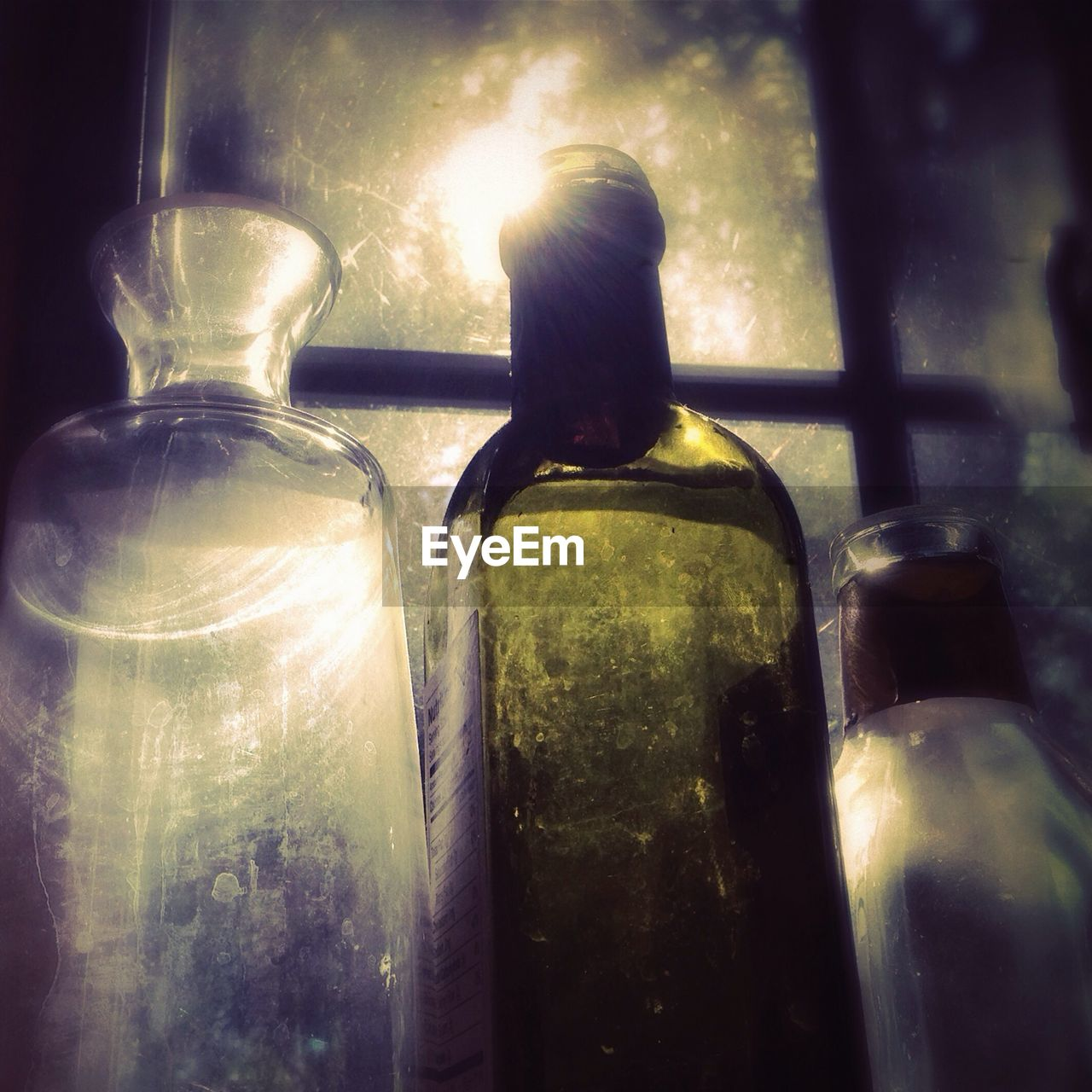 Close-Up Of Bottles Against Window