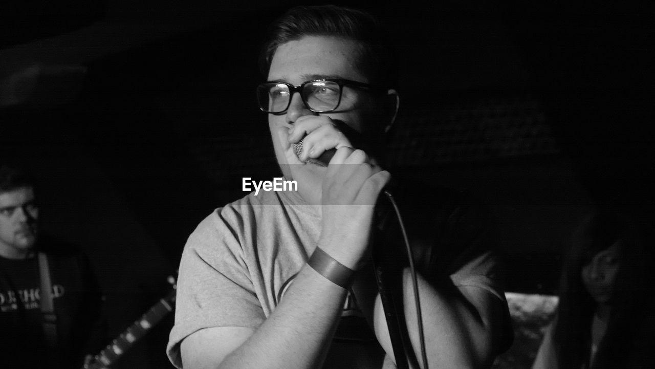 Musician looking away while singing at recording studio