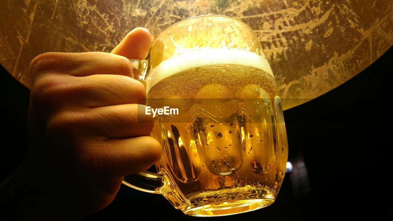 Close-up of cropped hand holding beer glass