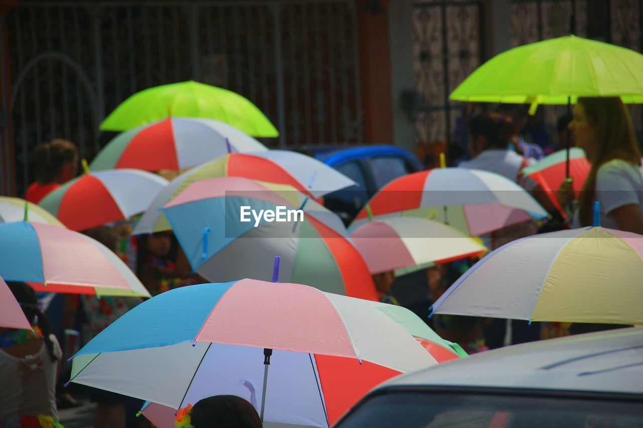 multi colored, protection, umbrella, security, real people, nature, group of people, rain, wet, day, outdoors, adult, people, men, group, safety, focus on foreground, water, rainy season, festival