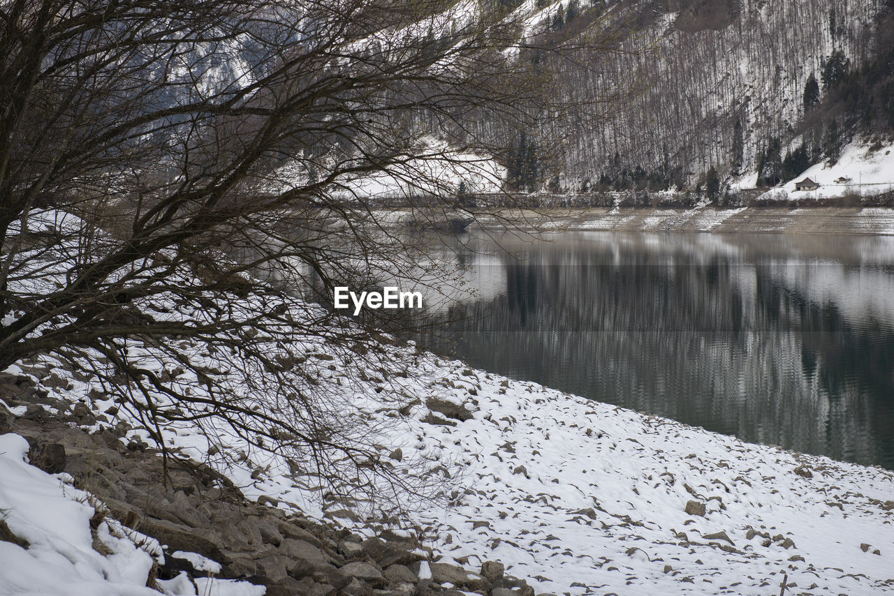 snow, cold temperature, winter, tree, beauty in nature, scenics - nature, plant, tranquility, water, nature, tranquil scene, bare tree, no people, day, non-urban scene, lake, covering, environment, outdoors, snowcapped mountain, flowing water