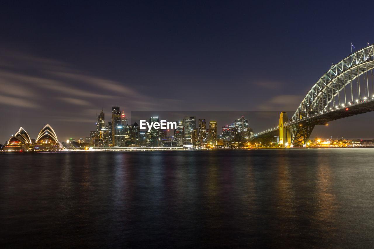 Illuminated bridge and cityscape against sky at night