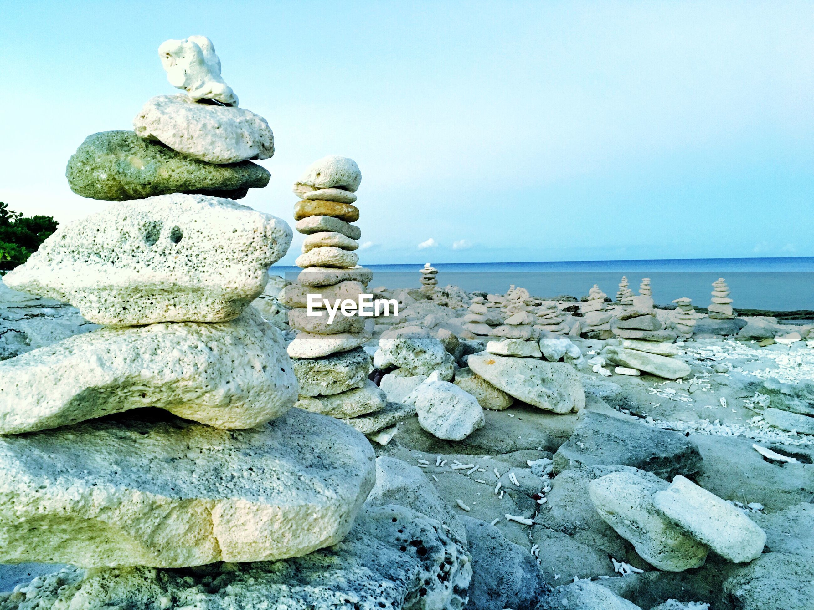 Stacked pebbles at beach against sky