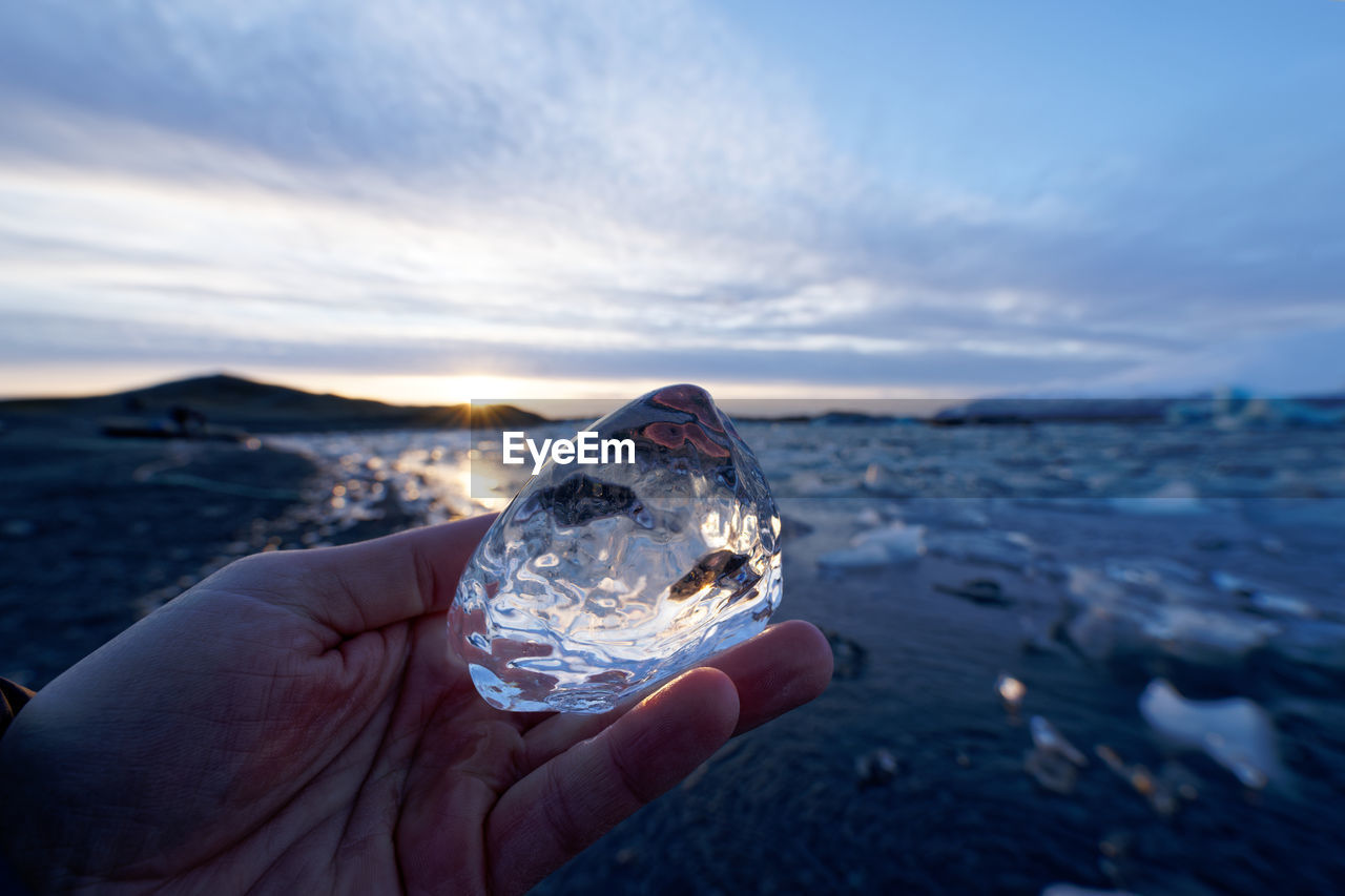 Cropped hand of person holding ice over sea against sky