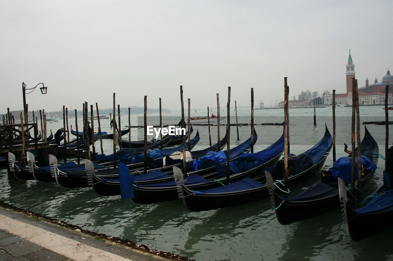 nautical vessel, moored, water, mode of transportation, transportation, gondola - traditional boat, post, sky, travel destinations, wooden post, nature, canal, architecture, building exterior, built structure, no people, wood - material, travel, waterfront, outdoors