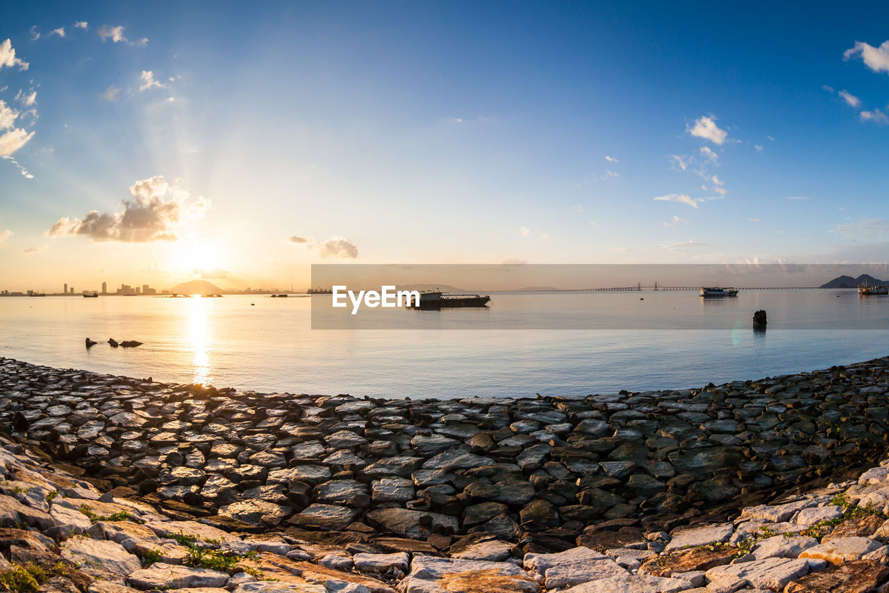 sky, water, cloud - sky, sunset, sea, scenics - nature, beauty in nature, transportation, solid, nature, rock, no people, tranquility, tranquil scene, sunlight, outdoors, idyllic, rock - object, non-urban scene, groyne, stone wall, pebble