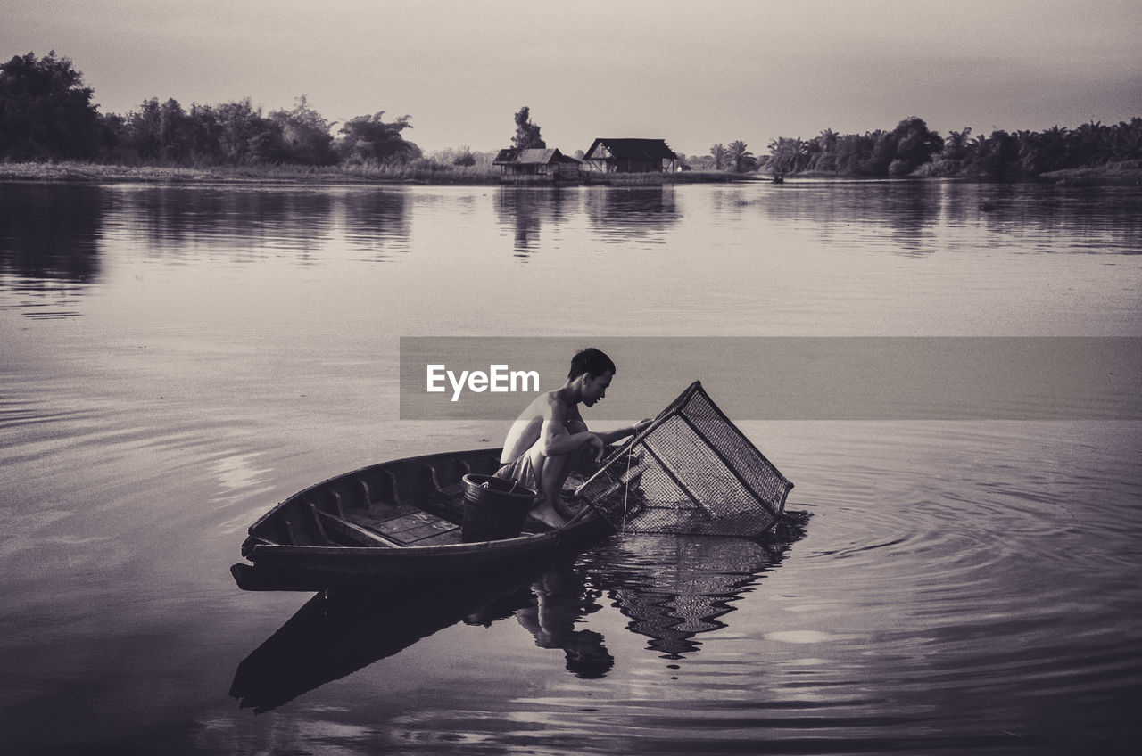 water, nautical vessel, lake, one person, reflection, transportation, mode of transportation, waterfront, real people, men, nature, oar, sky, sitting, lifestyles, day, rowing, outdoors, fisherman