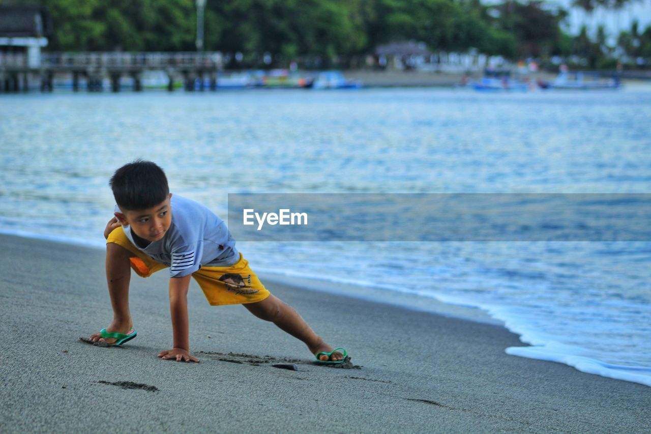 Full length of cute boy playing on shore at beach