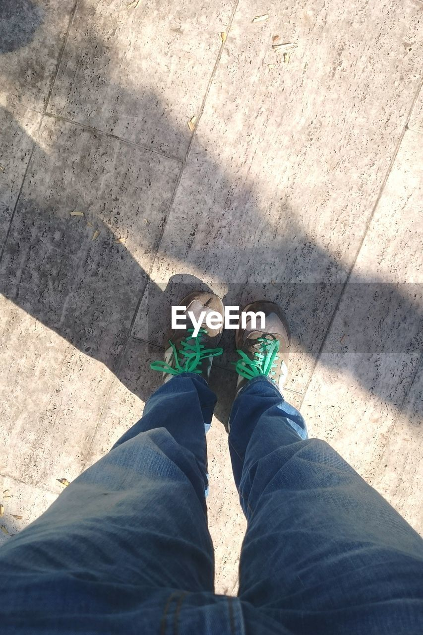 low section, human leg, shoe, one person, real people, high angle view, day, standing, shadow, personal perspective, casual clothing, lifestyles, human body part, leisure activity, outdoors, men, people