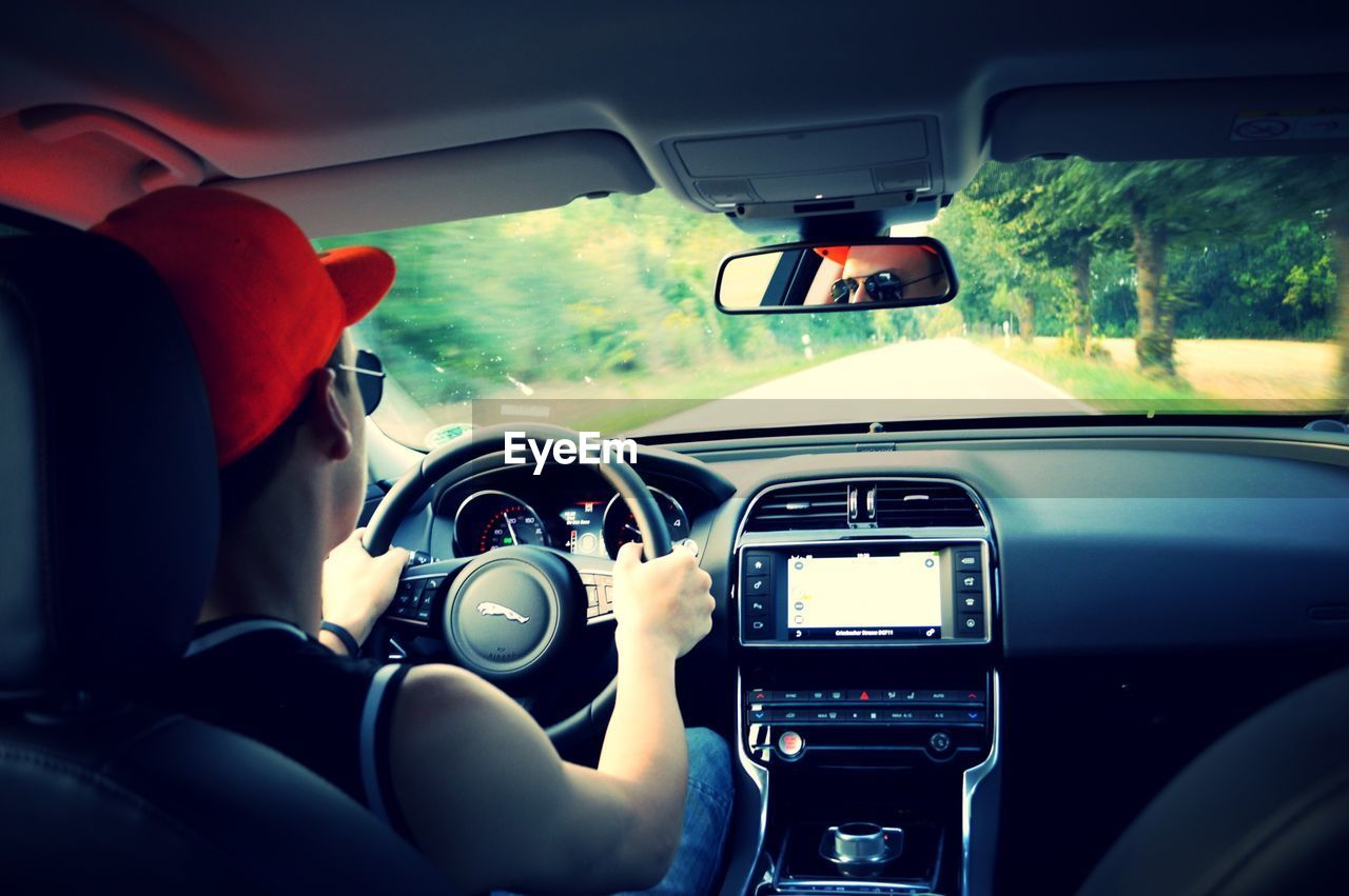 car interior, car, vehicle interior, steering wheel, driving, human hand, dashboard, transportation, human body part, land vehicle, one person, real people, windshield, men, travel, holding, journey, day, speedometer, close-up, nature, outdoors, people