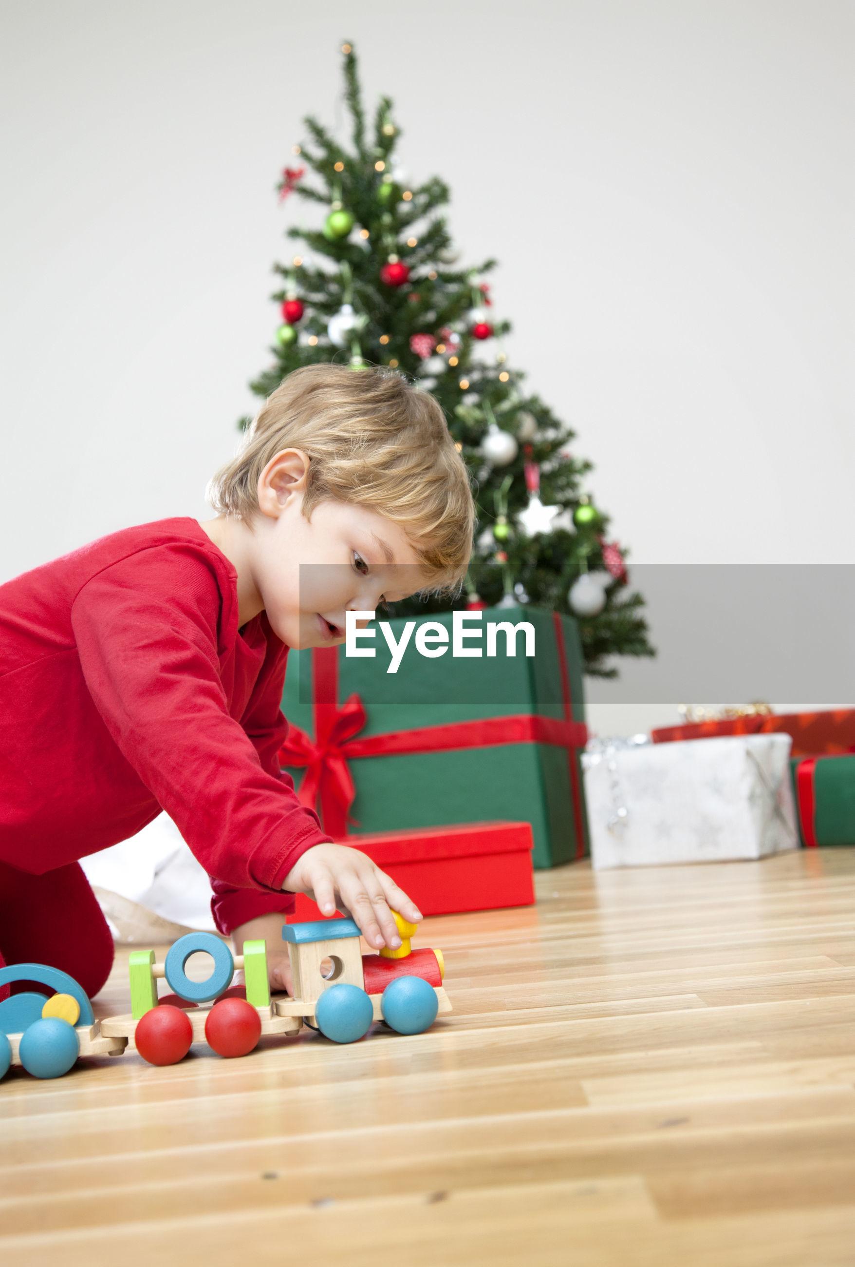 Boy and christmas tree at home