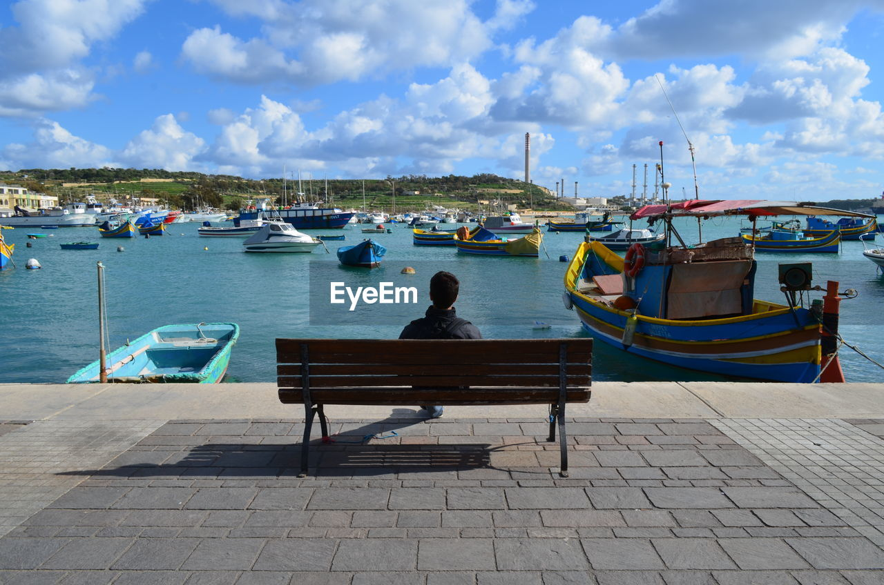 Rear View Of Man Sitting At Harbor Against Sky