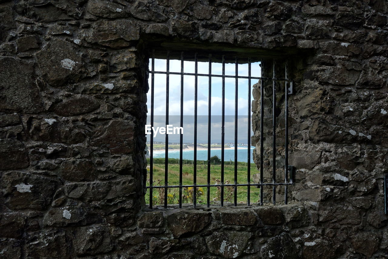 window, no people, architecture, built structure, wall, wall - building feature, day, plant, security, prison, building, outdoors, punishment, nature, protection, prison cell, building exterior, safety, closed, stone wall