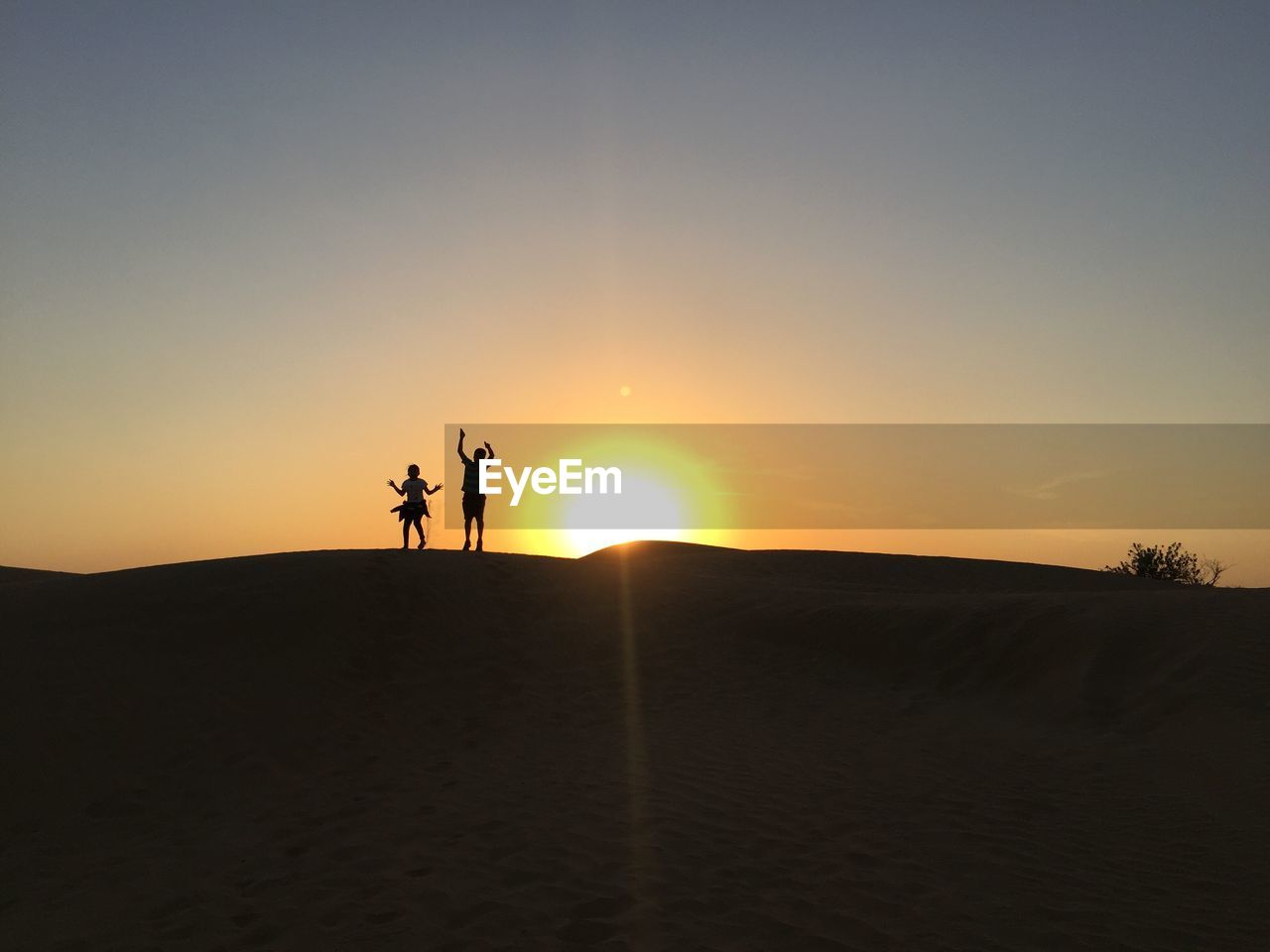 sunset, sky, silhouette, scenics - nature, land, orange color, sun, real people, beauty in nature, nature, tranquil scene, lifestyles, leisure activity, sunlight, tranquility, men, two people, landscape, non-urban scene, sand, outdoors, lens flare, arid climate