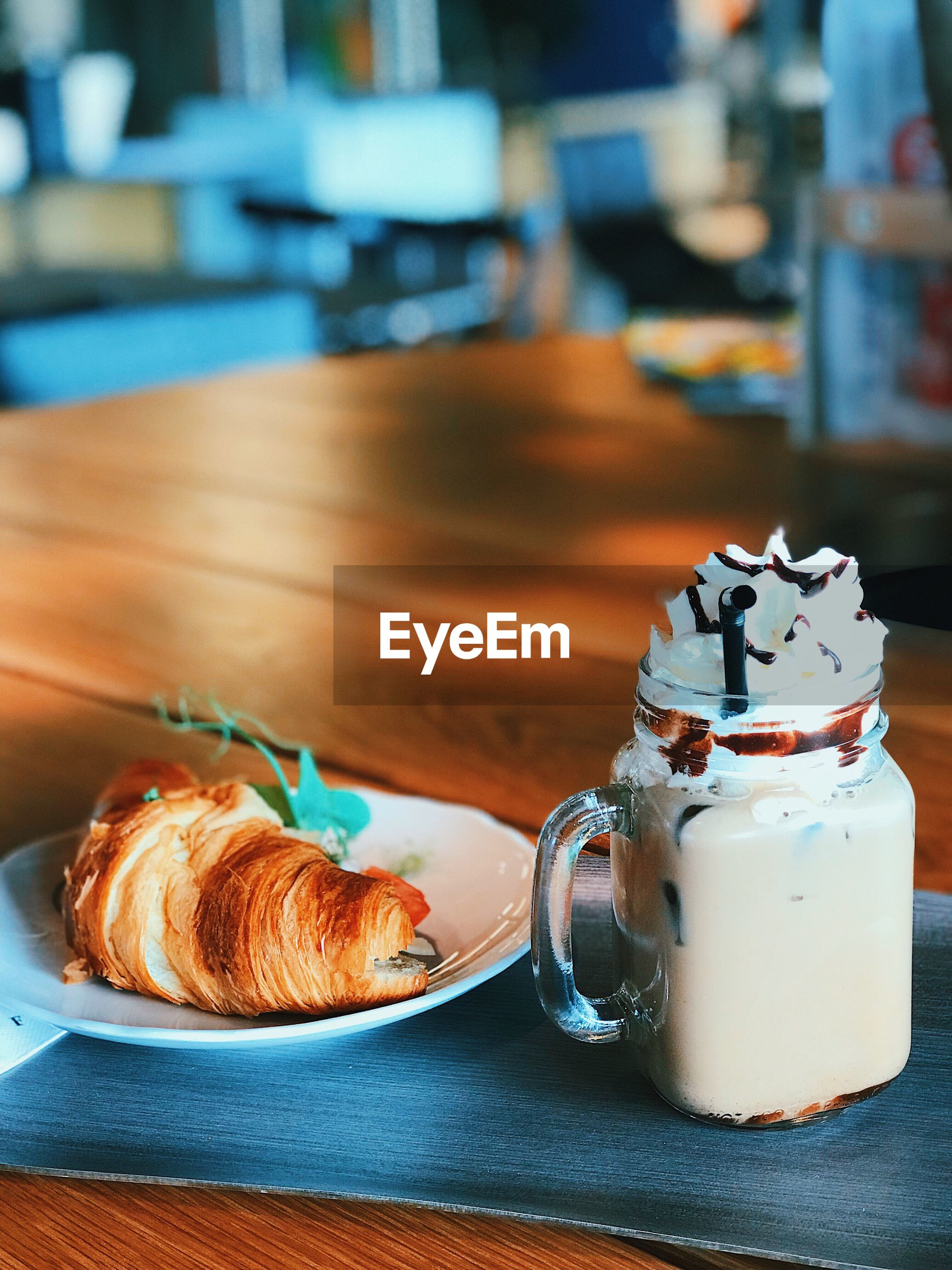 Close-up of croissant with iced coffee served on table in restaurant