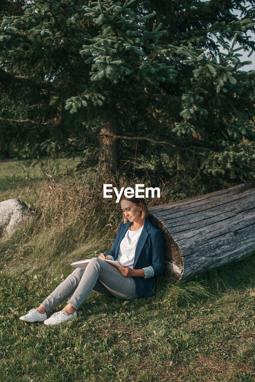 BEAUTIFUL YOUNG WOMAN SITTING ON LAND