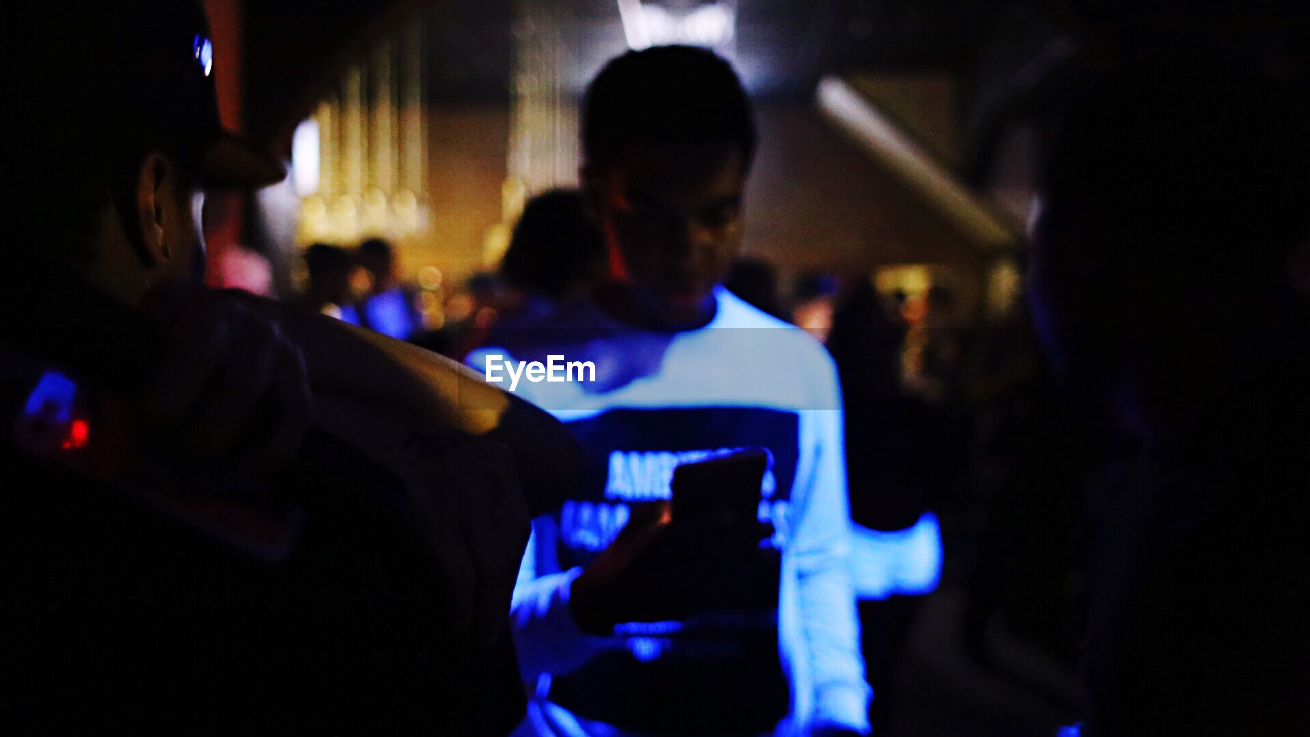 indoors, men, illuminated, lifestyles, technology, leisure activity, night, wireless technology, communication, photographing, music, holding, rear view, person, dark, photography themes, mobile phone, sitting