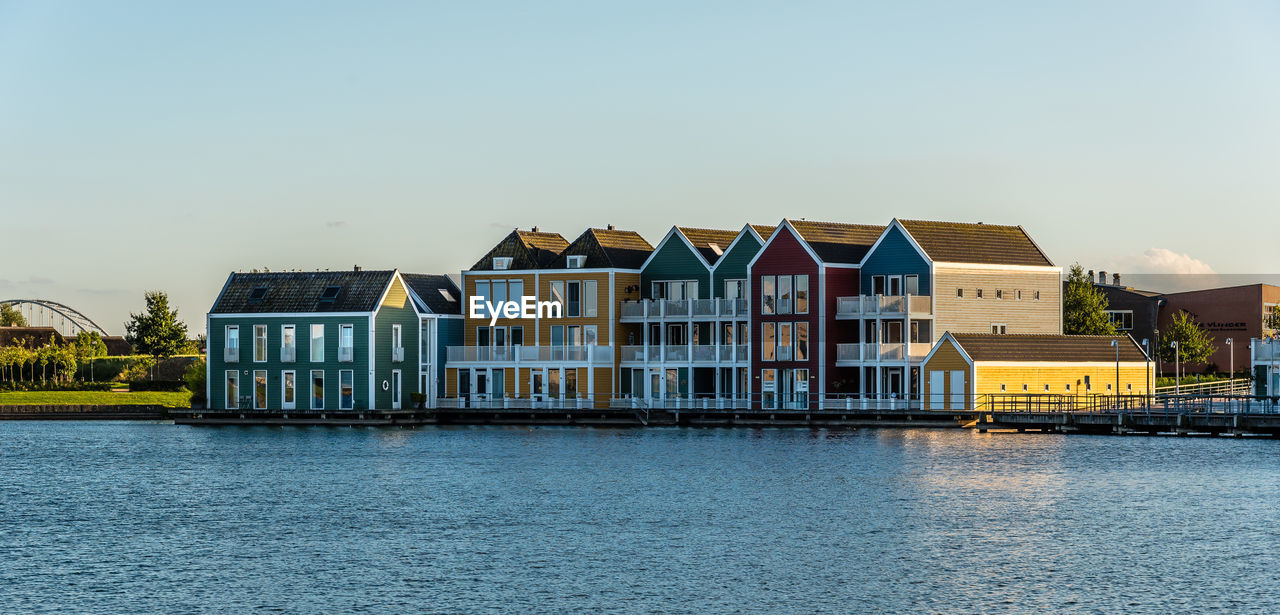 Colorful houses by river against clear sky