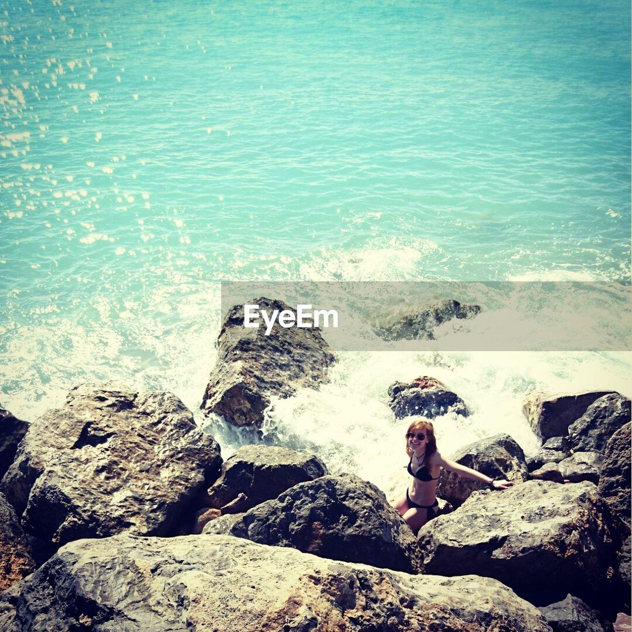 High Angle View Of Young Woman In Bikini Sitting On Rock By Sea