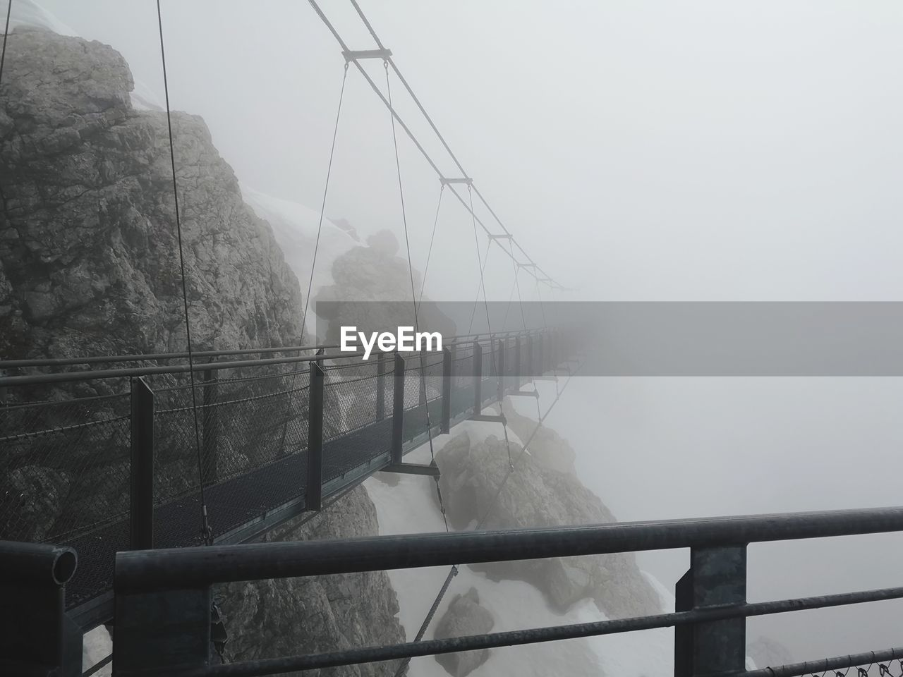 fog, railing, cold temperature, nature, winter, bridge, bridge - man made structure, day, real people, connection, transportation, snow, sky, outdoors, water, beauty in nature, architecture, built structure, lifestyles, footbridge