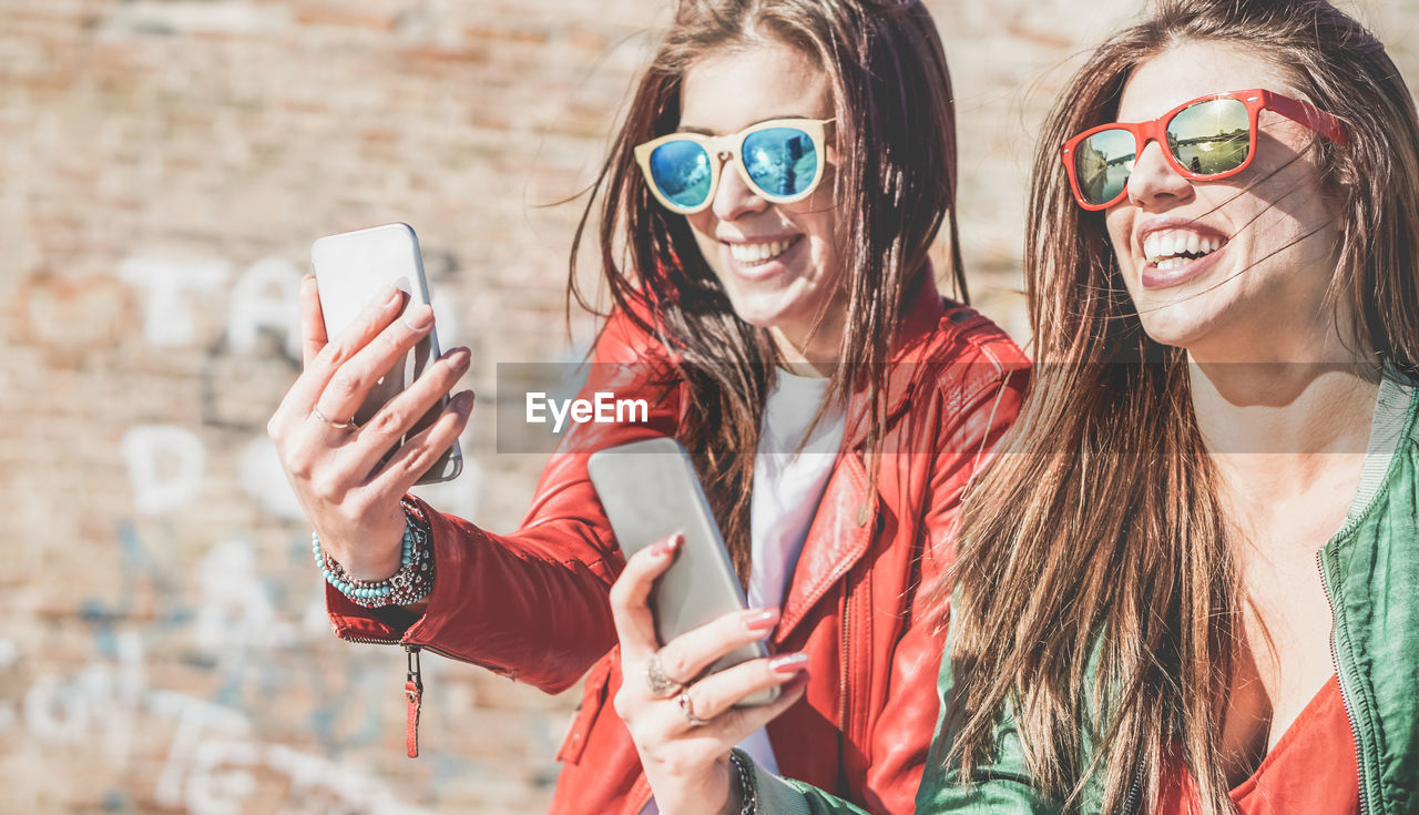 Happy Friends Taking Self Portrait On Mobile Phones During Sunny Day