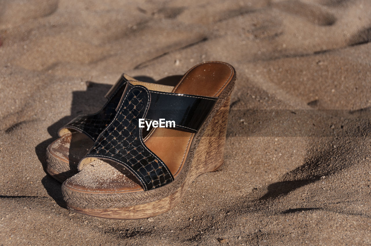 Close-up of abandoned sandals on sand