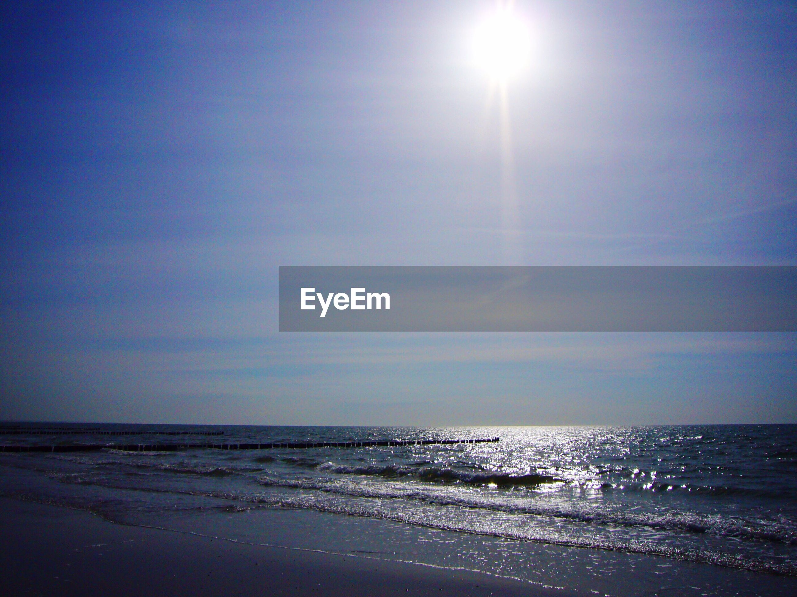 sea, horizon over water, beach, water, tranquil scene, tranquility, scenics, sun, shore, beauty in nature, sand, nature, sky, sunlight, idyllic, clear sky, sunbeam, blue, copy space, wave