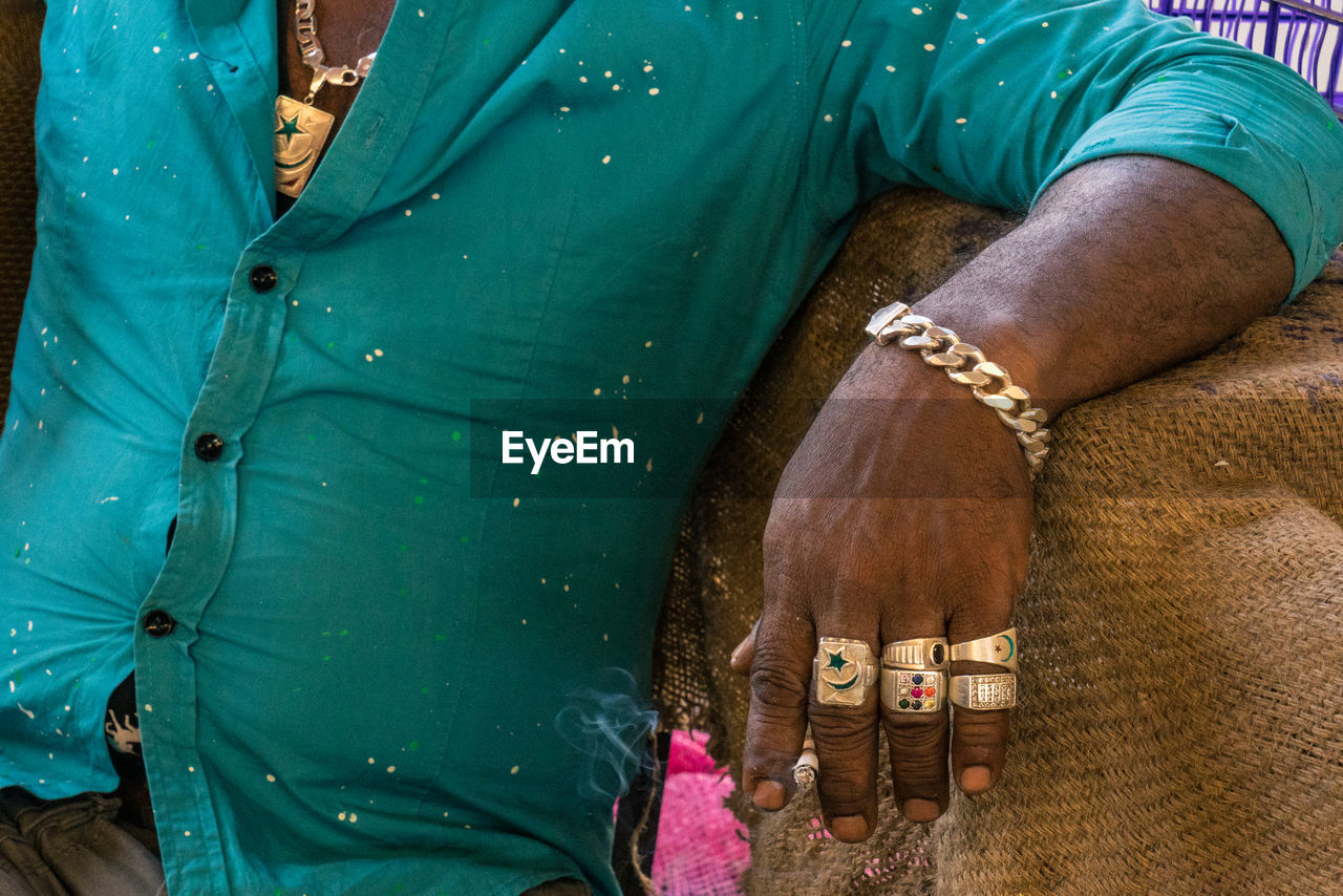 Midsection Of Man Wearing Golden Jewelries