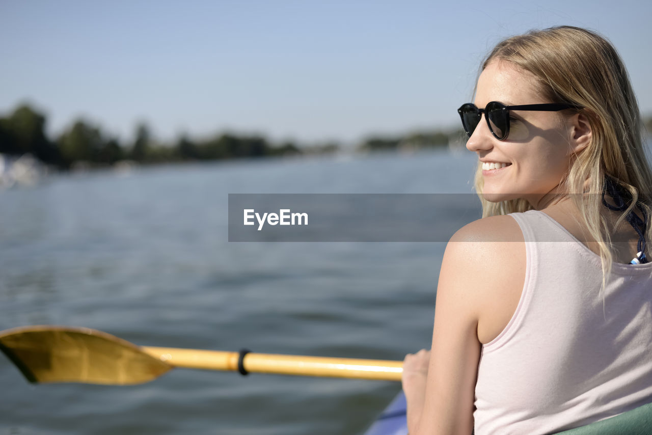 Rear View Of Young Woman Smiling While Sailing Boat In Lake