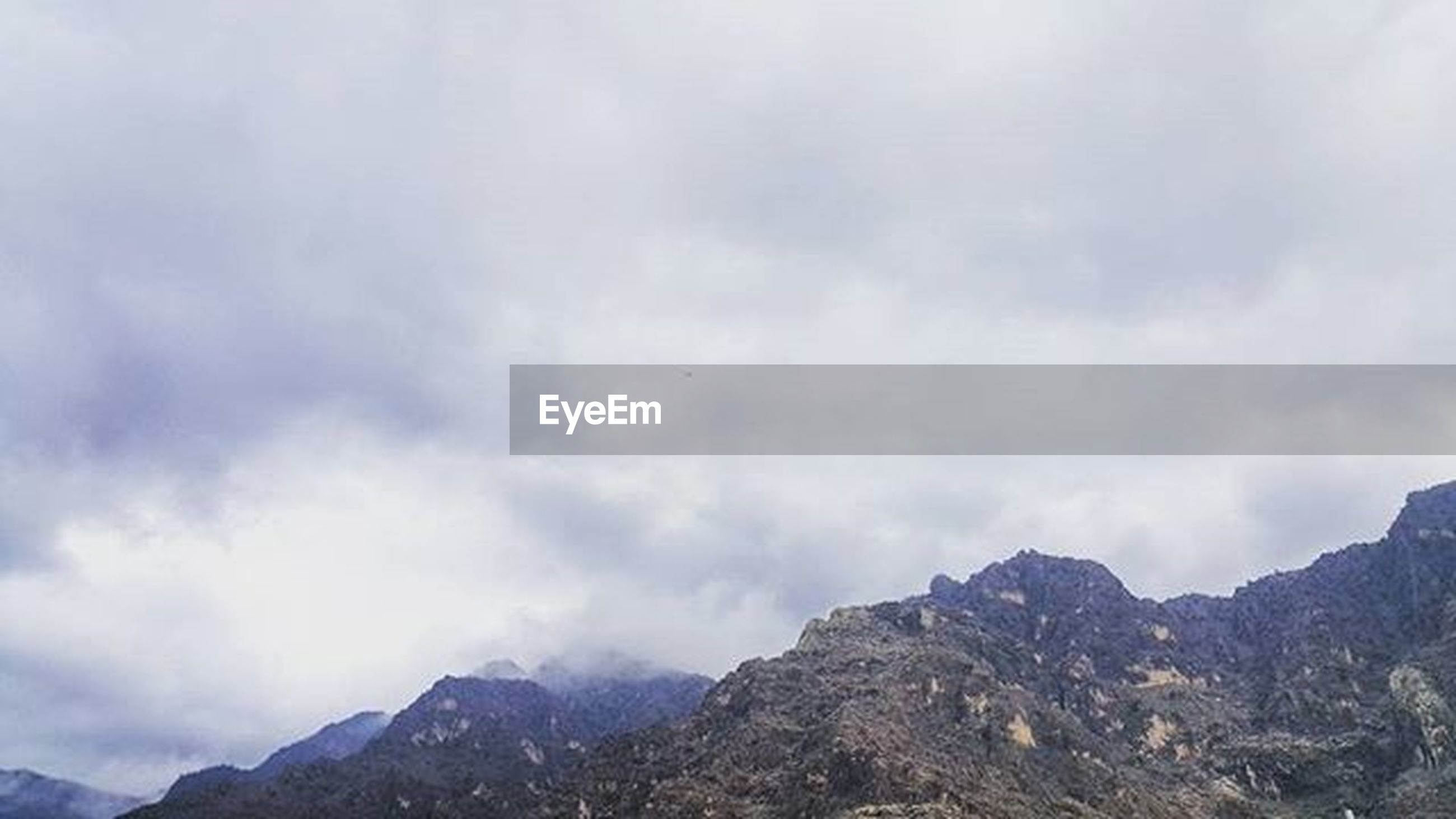 mountain, sky, scenics, tranquil scene, tranquility, cloud - sky, beauty in nature, mountain range, cloudy, nature, landscape, cloud, low angle view, weather, non-urban scene, idyllic, day, outdoors, no people, overcast