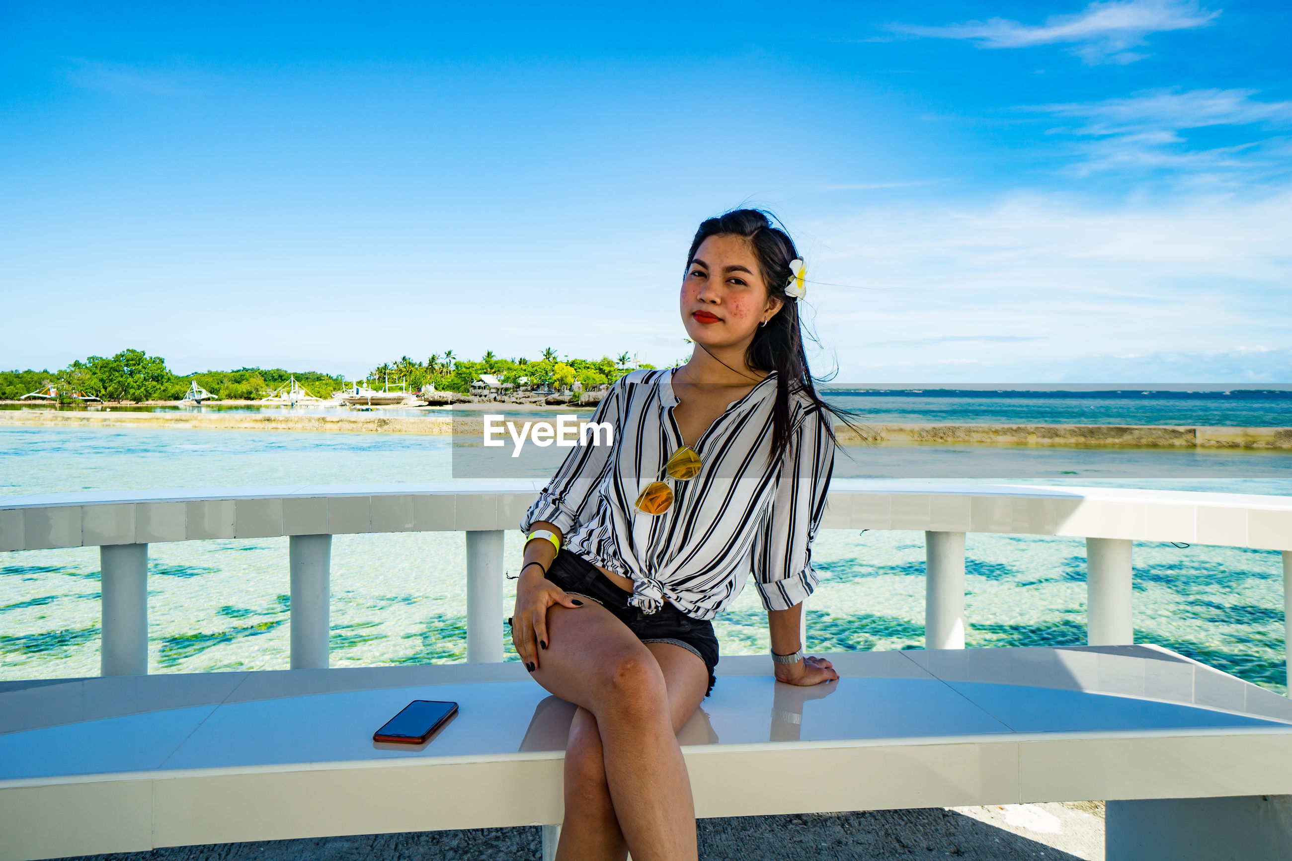 Young woman sitting by sea against blue sky