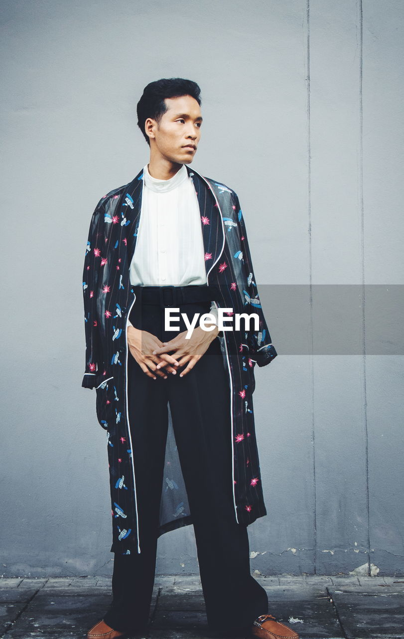 one person, standing, front view, real people, young adult, lifestyles, clothing, full length, casual clothing, young men, wall - building feature, leisure activity, traditional clothing, looking, portrait, young women, beautiful woman, contemplation, scarf