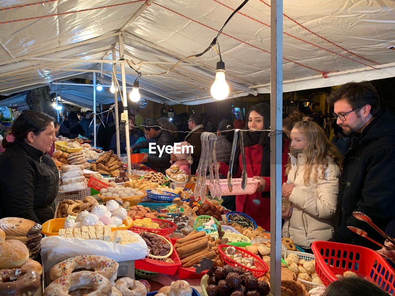 adult, retail, women, group of people, real people, illuminated, men, business, food and drink, people, market, customer, market stall, food, lighting equipment, waist up, choice, shopping, lifestyles, mid adult, buying, retail display