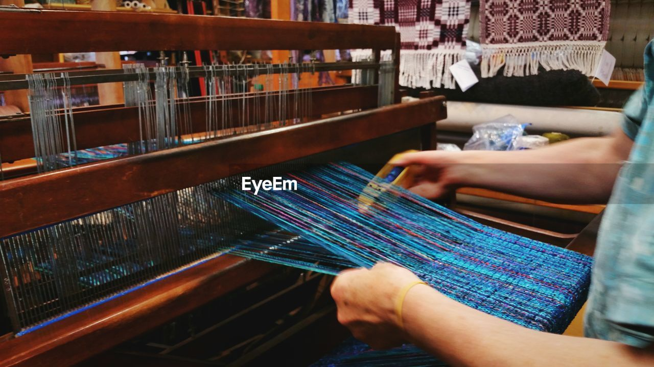 Midsection Of Woman Weaving Looms With Shuttle At Workshop