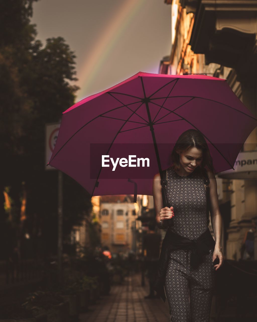 Woman with umbrella walking in city during sunset