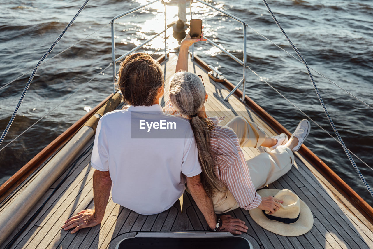 Rear view of friends sitting on boat sailing in sea