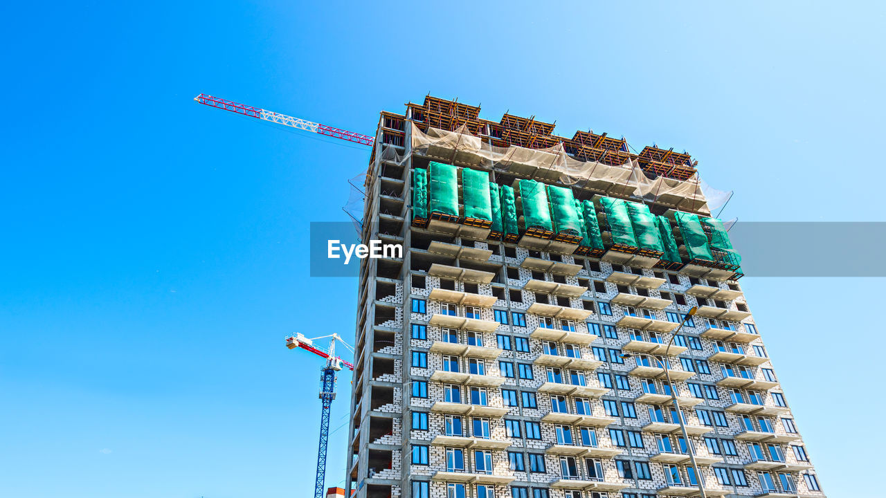 LOW ANGLE VIEW OF BUILDING AT CONSTRUCTION SITE AGAINST CLEAR SKY