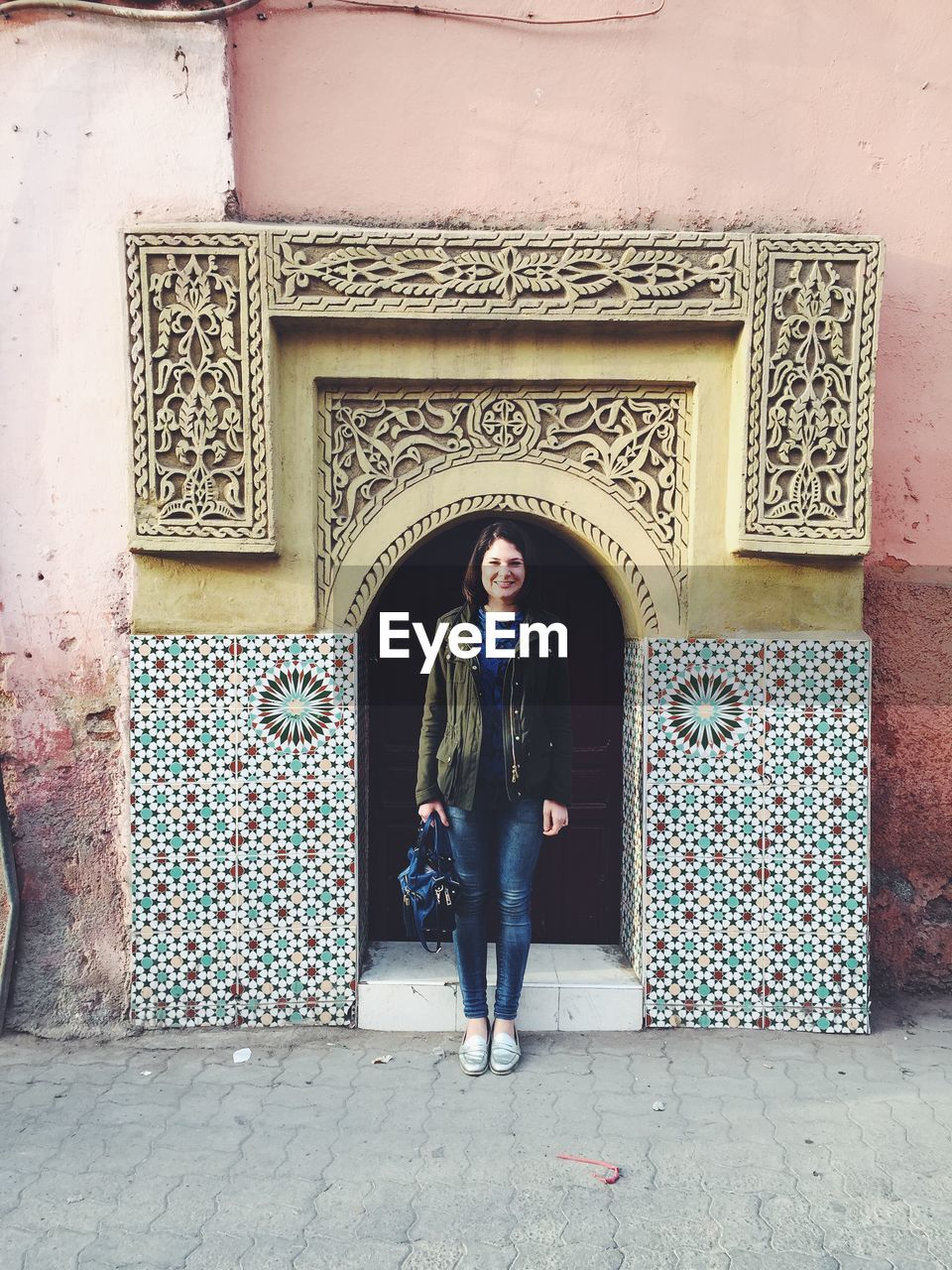 real people, door, entrance, one person, built structure, front view, casual clothing, full length, architecture, doorway, lifestyles, day, standing, leisure activity, outdoors, building exterior, young women, pattern, architectural column, young adult, portrait, beautiful woman