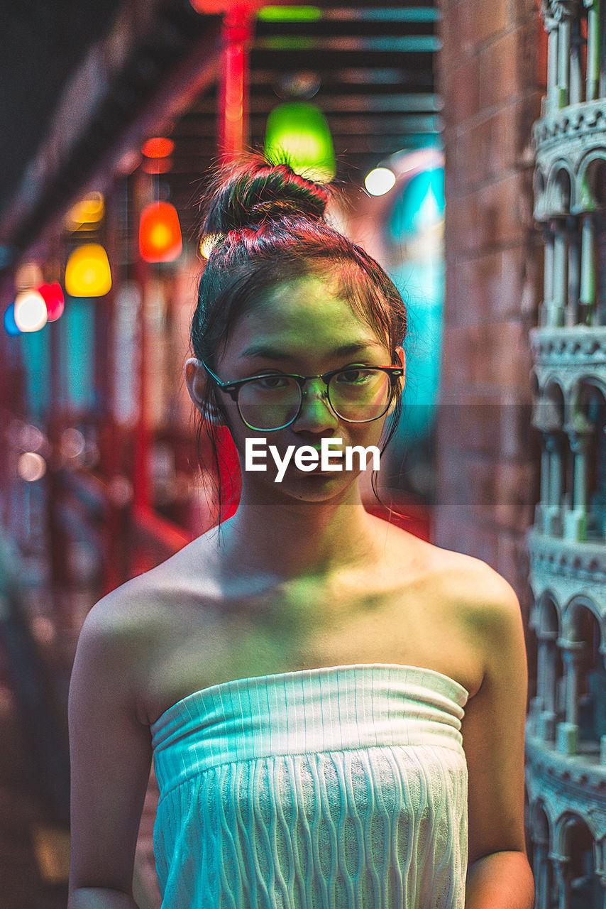 Portrait Of Teenage Girl Wearing Eyeglasses At Night