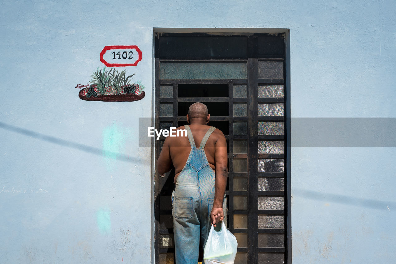 Rear view man with plastic bag standing against closed door of house