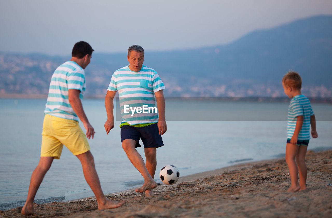 water, togetherness, men, males, beach, boys, casual clothing, child, real people, land, leisure activity, childhood, soccer, two people, sky, sea, nature, lifestyles, day, outdoors