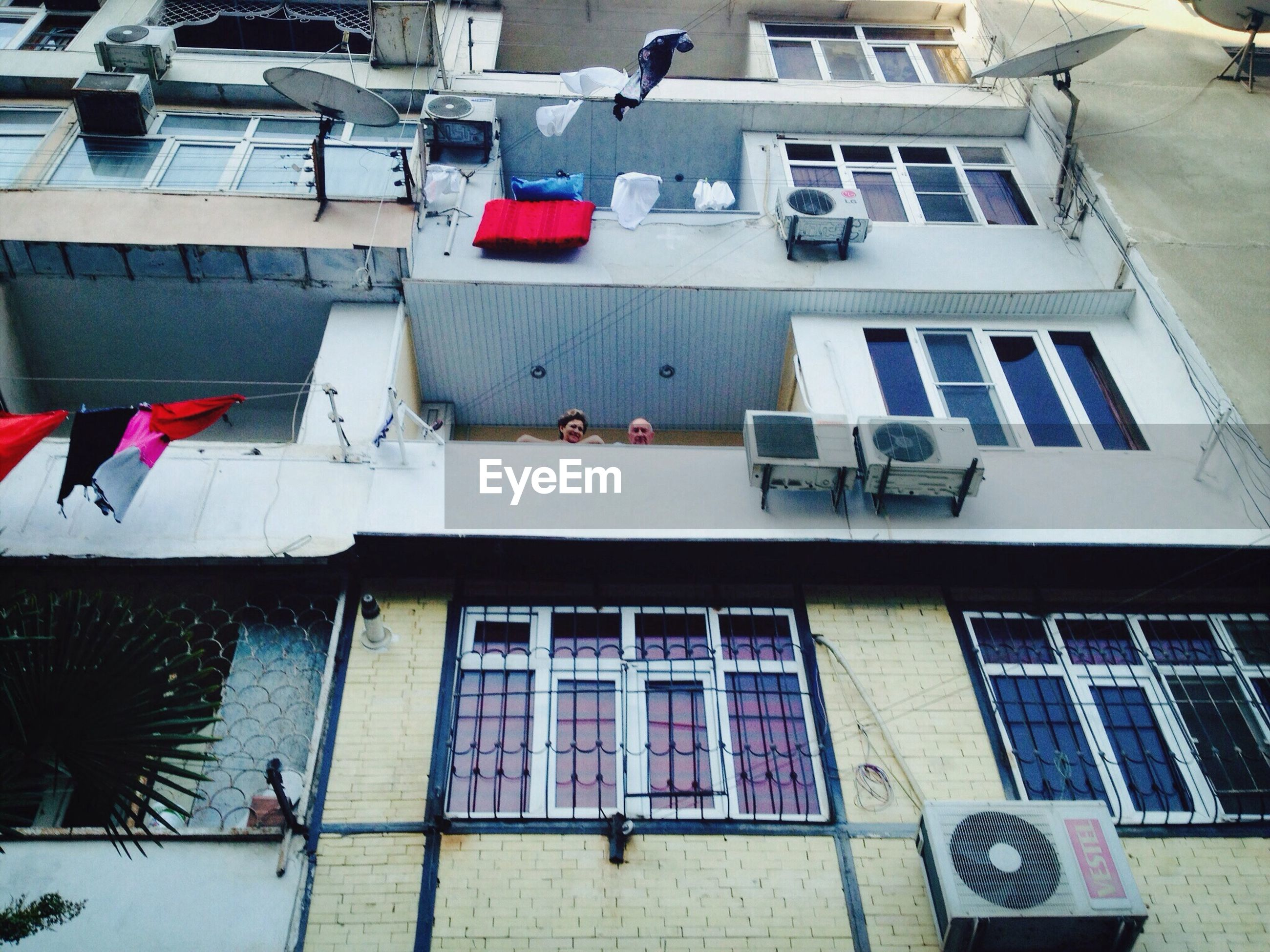 building exterior, architecture, built structure, residential building, hanging, building, residential structure, low angle view, window, clothesline, laundry, day, house, drying, flag, balcony, city, outdoors, in a row, no people