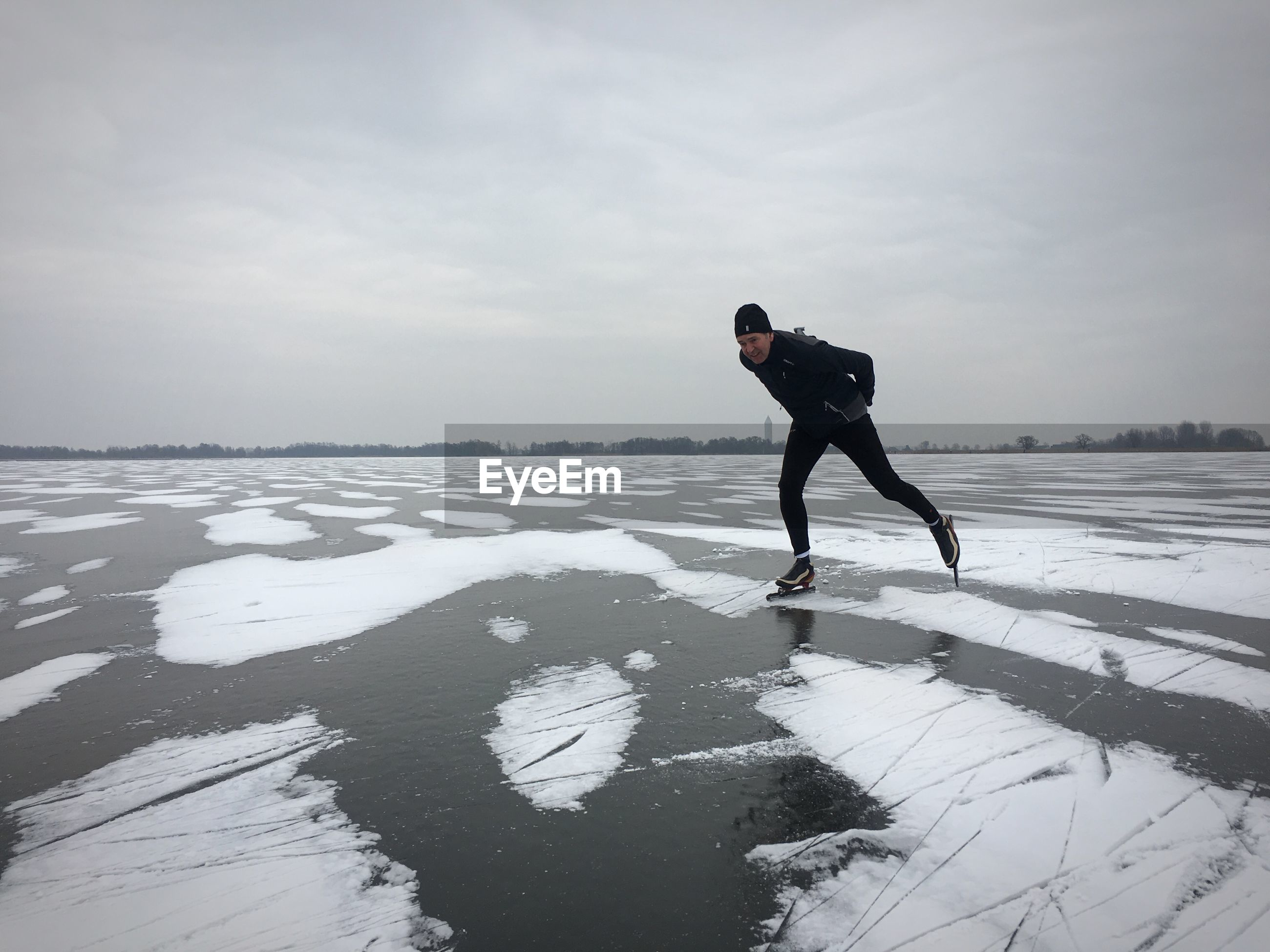 Man skating on ice rink against sky