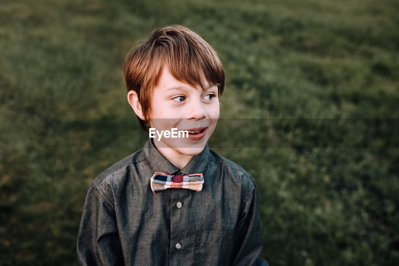 Smiling boy looking away while standing outdoors
