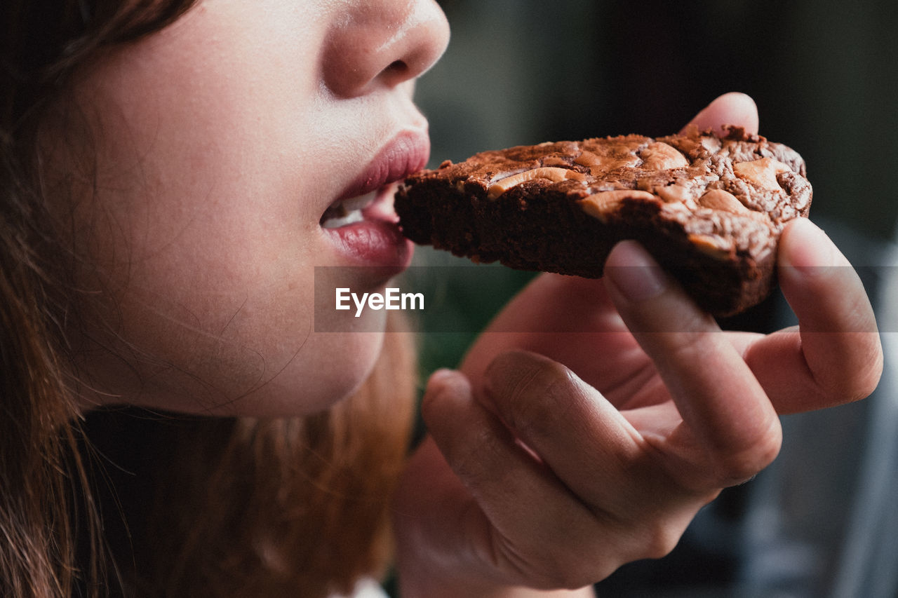 Midsection of young woman eating cake