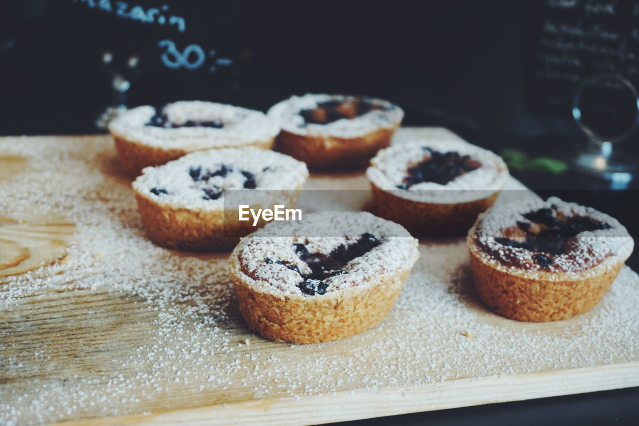 Close-Up Of Chocolate Cupcakes With Powdered Sugar At Bakery