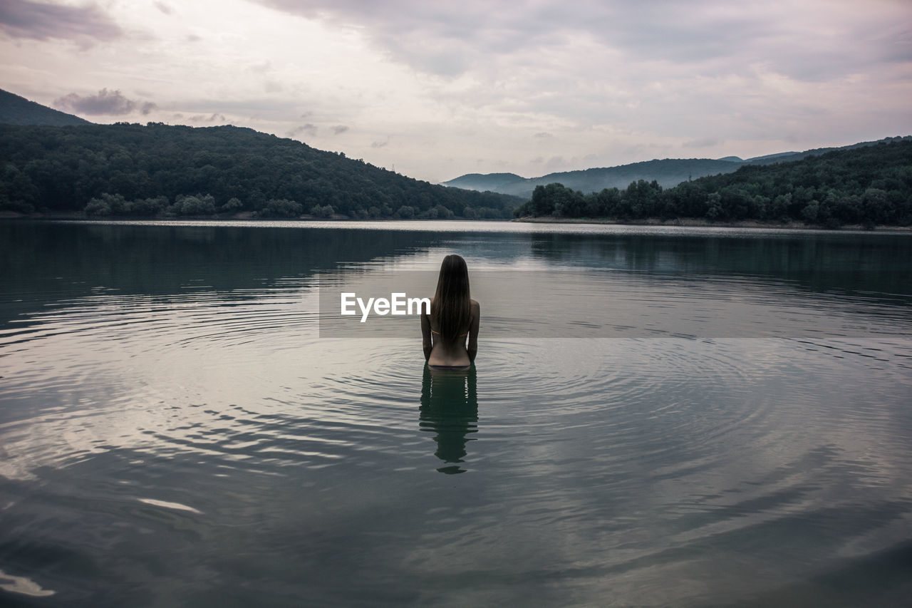Young Woman Standing In Lake Against Sky During Sunset