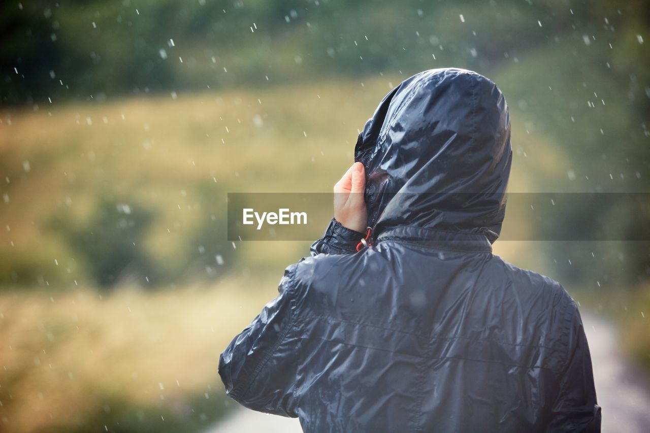 Rear view of man wearing raincoat on rainy day