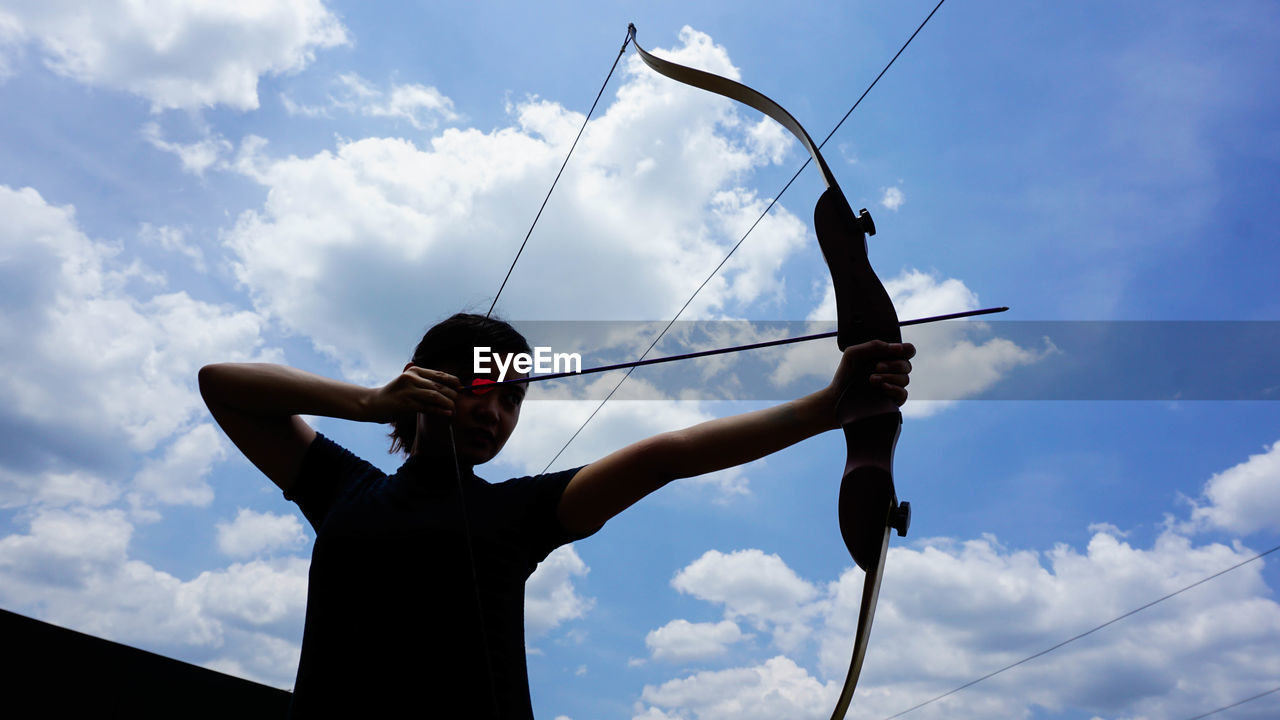 Low Angle View Of Woman Holding Bow And Arrow While Standing Against Sky